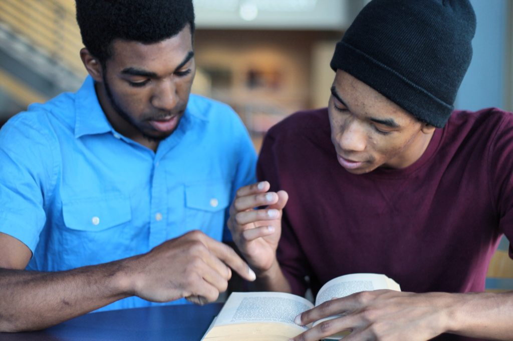 Two men or teen guys studying together