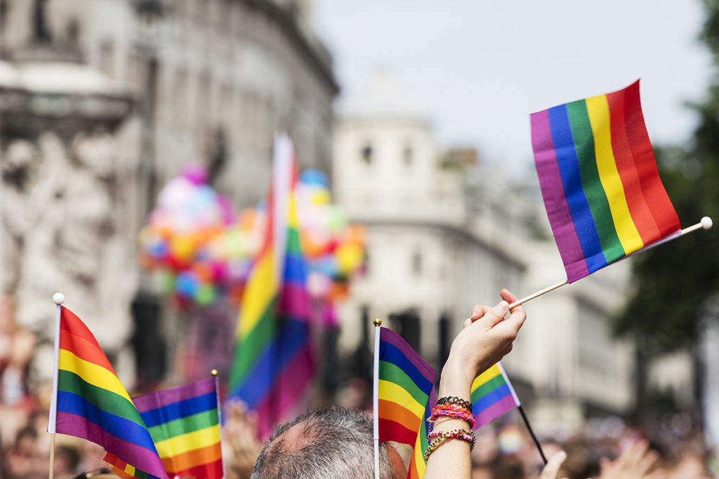 Hands holding Pride flags