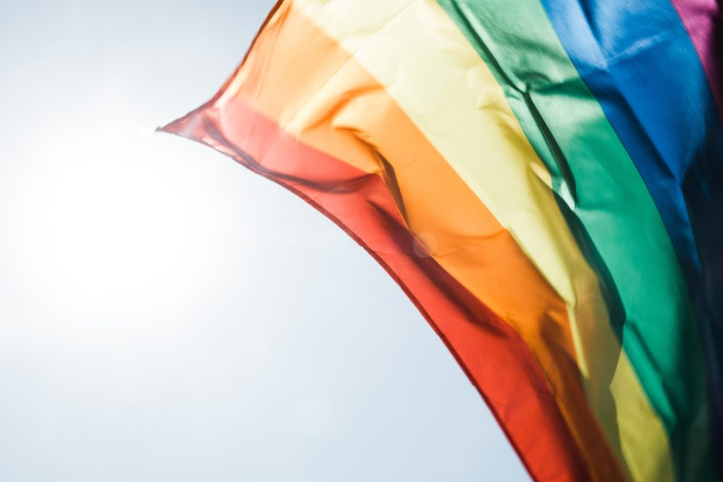 Image of the corner of Pride/Rainbow flag flying in front of a bright sky