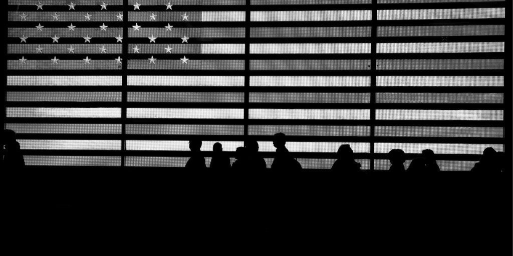American flag with people walking in front