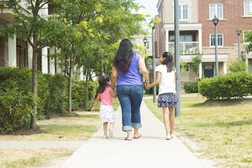 mother and two children walking down sidewalk in the sunshine