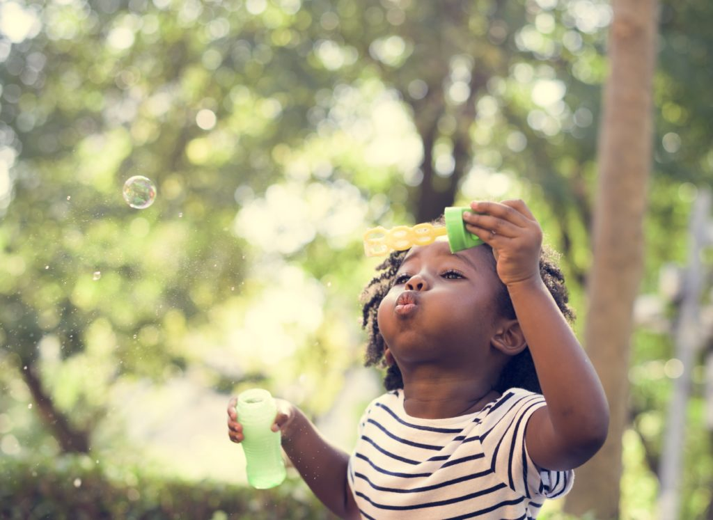 Young child blowing bubbles outside on a spring day
